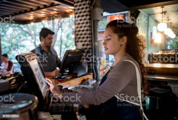 Woman working at the cashier at a restaurant picture id908849894?b=1&k=6&m=908849894&s=612x612&h=pqeuruzltxp1qkav1pxr1py1snw hqvswmndfdd0rky=