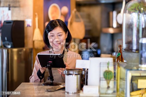 istock Woman working at the cashier at cafe 1149170645
