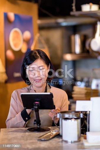 istock Woman working at the cashier at cafe 1149170651