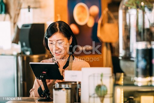 istock Woman working at the cashier at cafe 1150936184