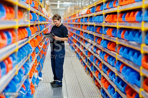 Woman with checklist examining red and blue trays on shelves in the aisle of warehouse