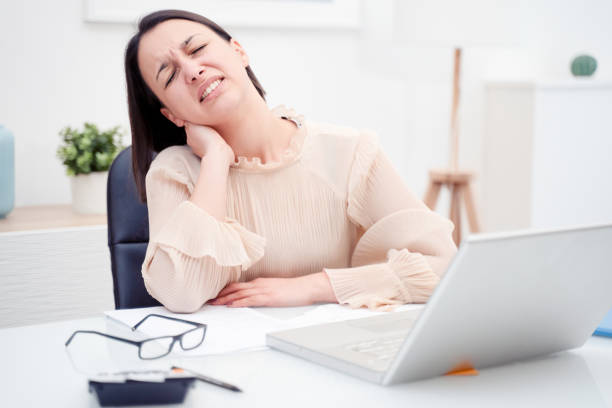 Woman working from home and feeling backache stock photo