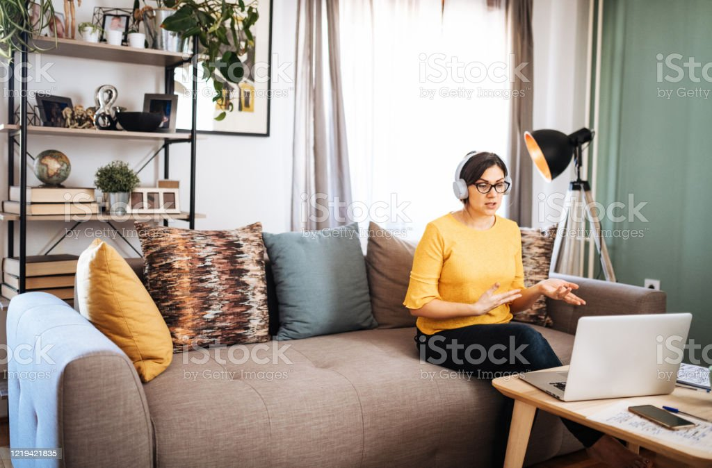 Woman working from home and having online business meeting Due to lockdown and quarantine orders, woman working from home and having online meetings with colleagues. Woman is in late 30s working from authentic living room. 30-39 Years Stock Photo