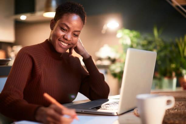 mujer trabajando desde casa, escribiendo a mano un documento. - black people fotografías e imágenes de stock