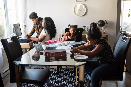 Woman in her thirties working from home in a small space. She is from African ethnicity and have long wavy hair. She is sitting in front of a table computer and a window. Her three children are around, doing homework on dinning room table. Horizontal full length indoors shot with copy space.