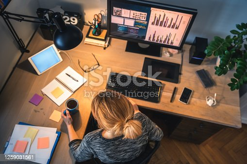 Woman working on computer in her home office during pandemic quarantine. Overhead view.