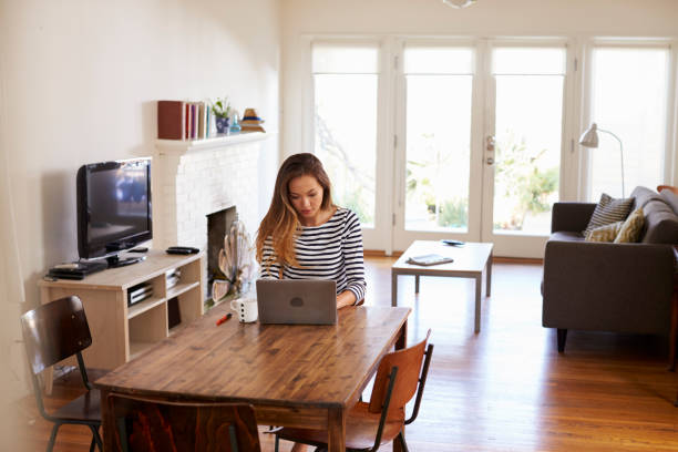 woman working from home using laptop on dining table - trabalhando de casa - fotografias e filmes do acervo