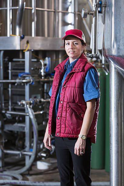 Woman working in a brewery standing by storage tanks stock photo