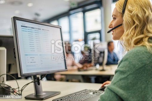 Blonde woman with a headset with a microphone using a computer while talking to a customer in a call center.