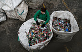 Woman working in a recycling center sorting some bottles and looking very happy - environmental concepts