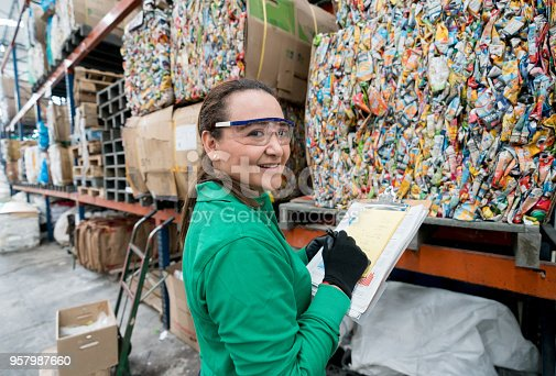 Portrait of a happy woman working in a recycling factory sorting the garbage and writing on a clipboard - environmental concepts
