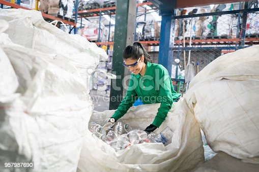 Woman working in a recycling factory sorting some bottles and looking very happy - environmental concepts