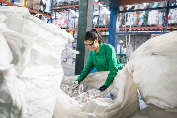 mujer que trabaja en una fábrica de reciclaje - cuestiones ambientales fotografías e imágenes de stock