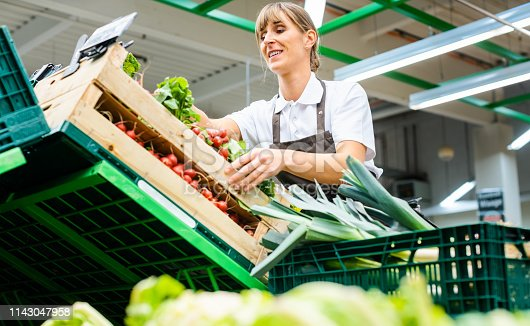 Woman working in a supermarket sorting fresh fruit and vegetables