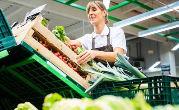 Frau, die in einem Supermarkt arbeitet und Obst und Gemüse sortiert – Foto