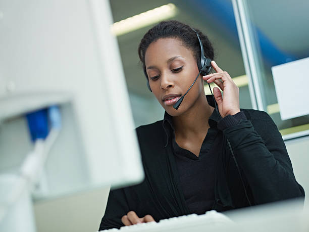 woman working in call center female african american customer service representative with headset typing on computer. Horizontal shape, front view, waist up hands free device stock pictures, royalty-free photos & images