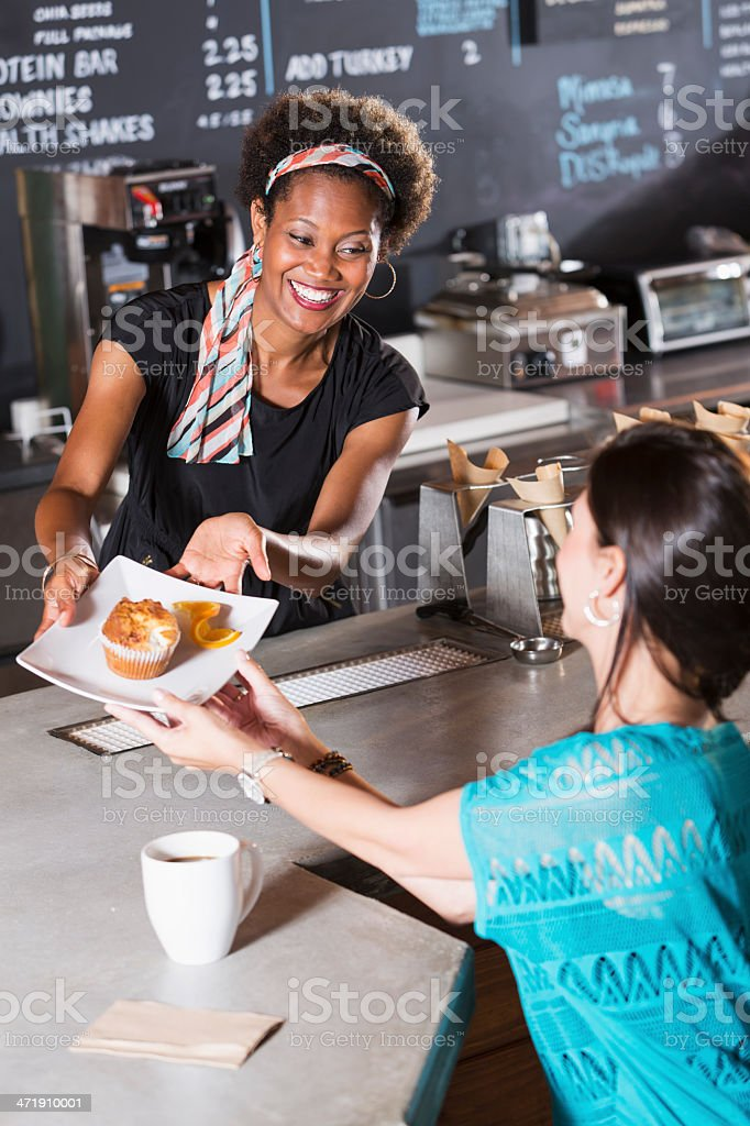 Woman working in coffee shop, serving customer stock photo