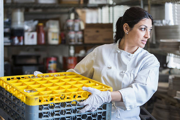 woman working in commercial kitchen - commercial dishwasher stock photos and pictures