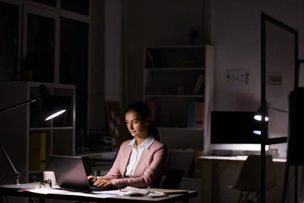 mujer que trabaja en oficina oscura - trabajar hasta tarde fotografías e imágenes de stock