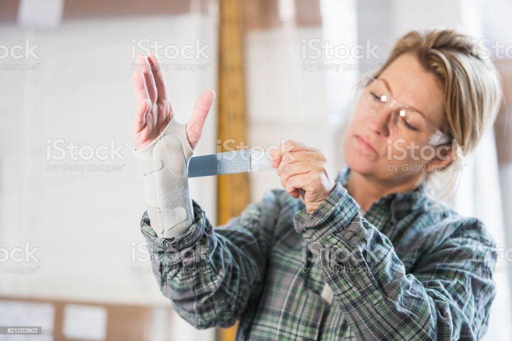 Woman working in factory putting brace on wrist stock photo