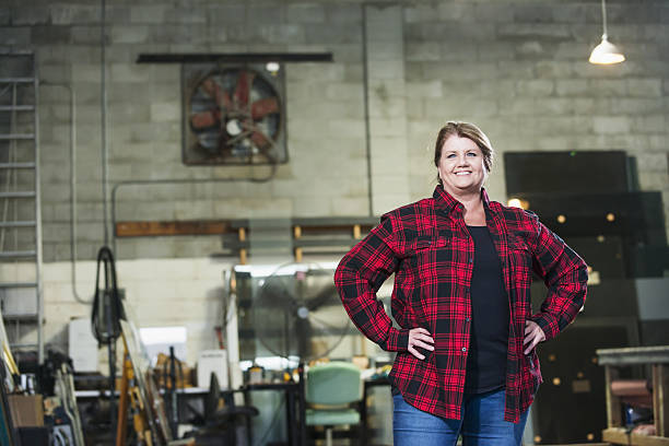 Woman working in factory warehouse A mature woman in her 50s standing with hands on hips, a worker in a factory warehouse. She is wearing a plaid shirt and jeans. A desk, worktable, equipment and supplies are out of focus in the background. plaid shirt stock pictures, royalty-free photos & images
