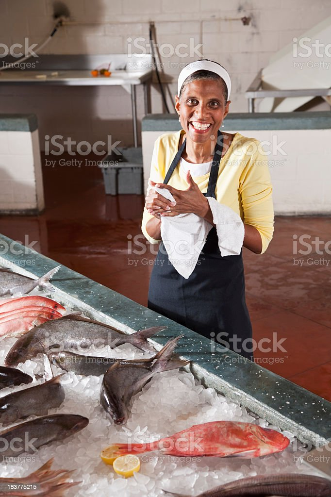 Woman working in fish market stock photo