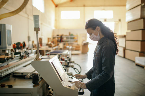 Woman working in industry at machine stock photo