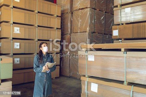 Mature woman working in industrial distribution warehouse. She is walking between big containers and checking quality and shipping list. She wears protective mask and gloves.