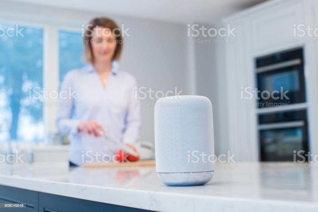 Frau arbeitet In der Küche mit Smart Speaker im Vordergrund – Foto