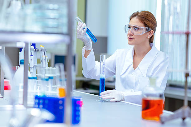 Woman working in laboratory on experiment with chemicals stock photo