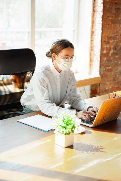 Woman working in office alone during coronavirus or COVID-19 quarantine, wearing face mask stock photo