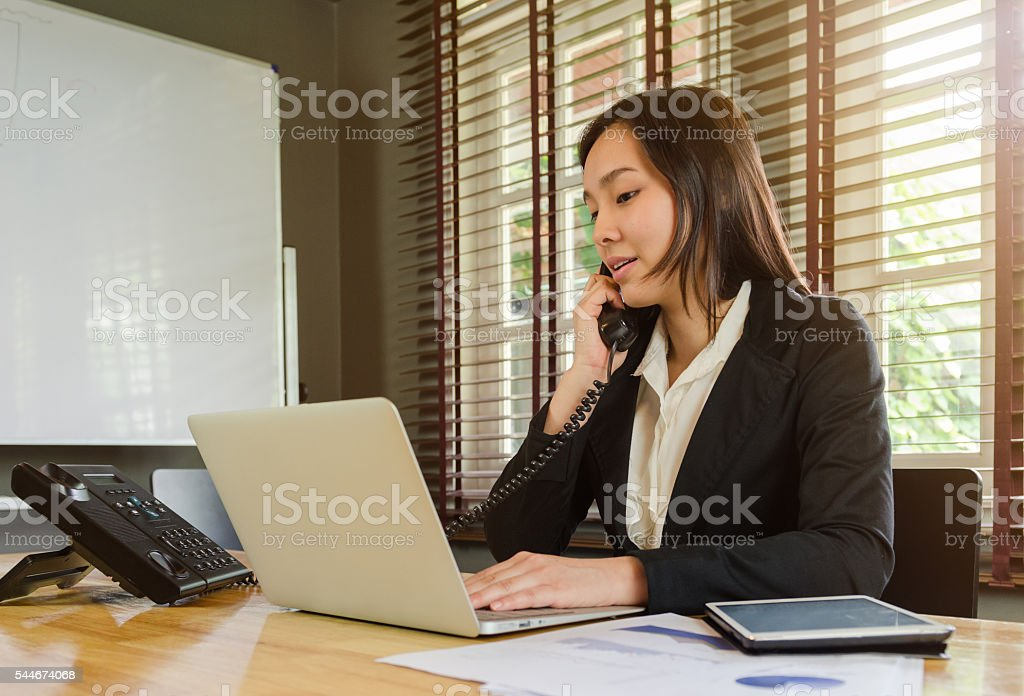 woman working in office and talking telephone stock photo