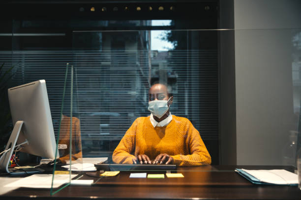 Woman working in respect to all the pandemic rules wearing mask and behind the glass stock photo