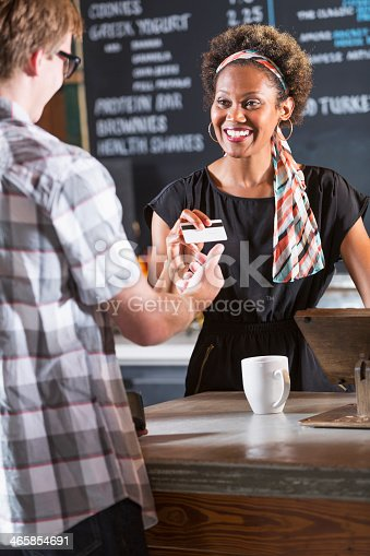 istock Woman working in restaurant taking payment from customer 465854691