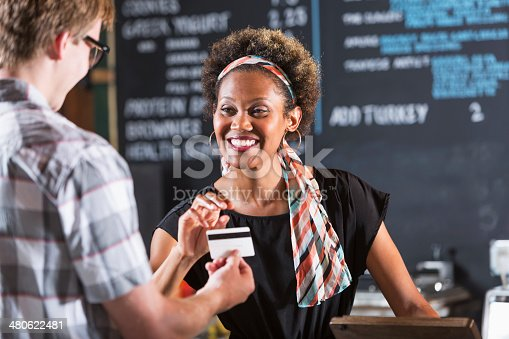istock Woman working in restaurant taking payment from customer 480622481