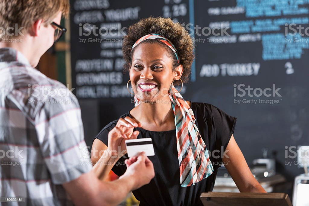Woman working in restaurant taking payment from customer stock photo