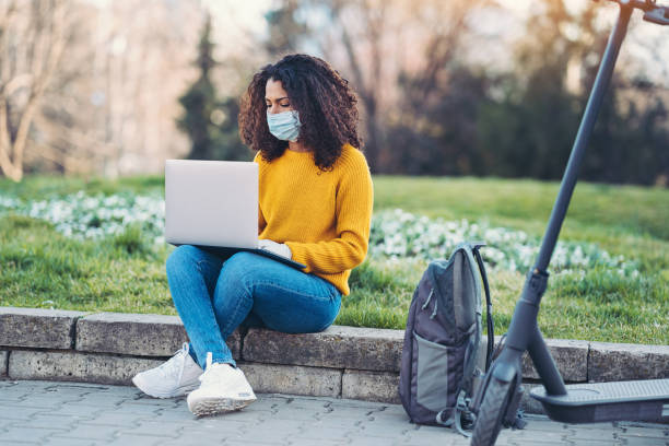 Woman working in the park during coronavirus social isolation Woman wearing a face mask working on a laptop outdoors in a park flatten the curve stock pictures, royalty-free photos & images