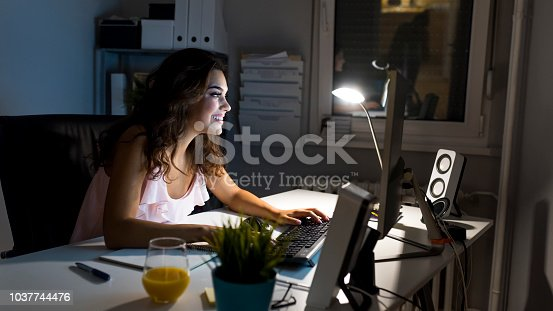 istock Woman working late at night at home 1037744476