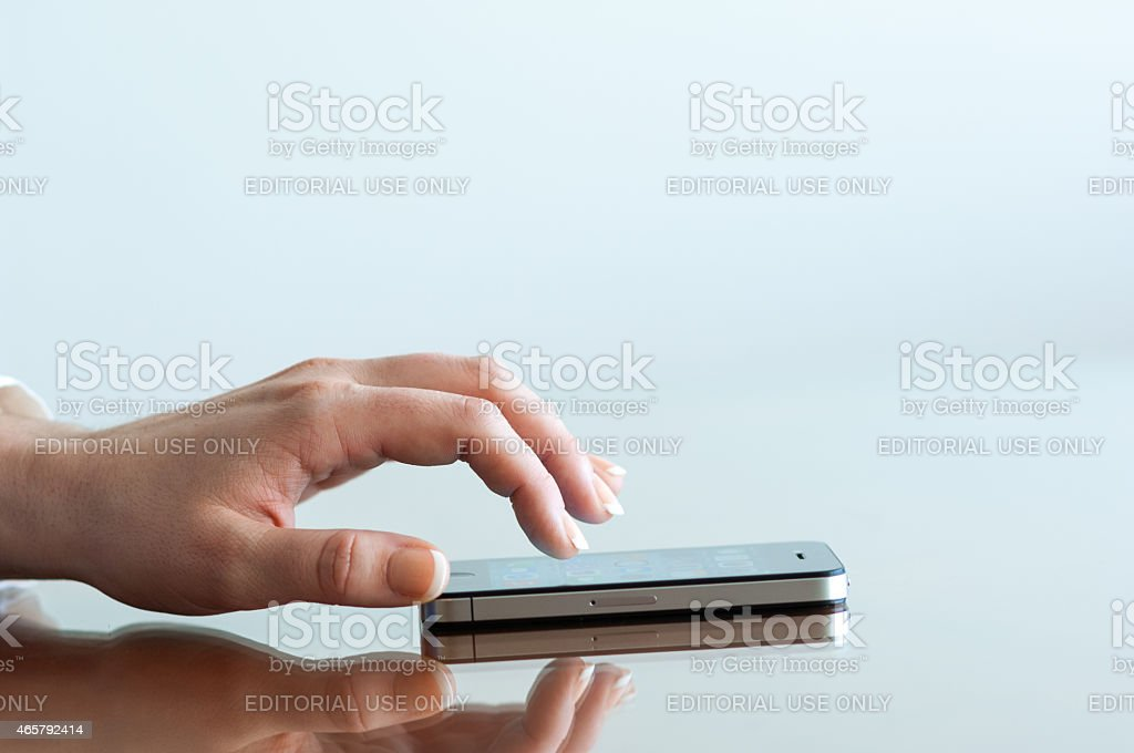 Woman working on a black Apple iPhone 4 stock photo