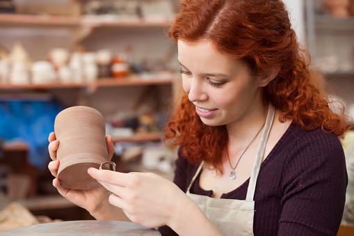 Woman working on a clay vase