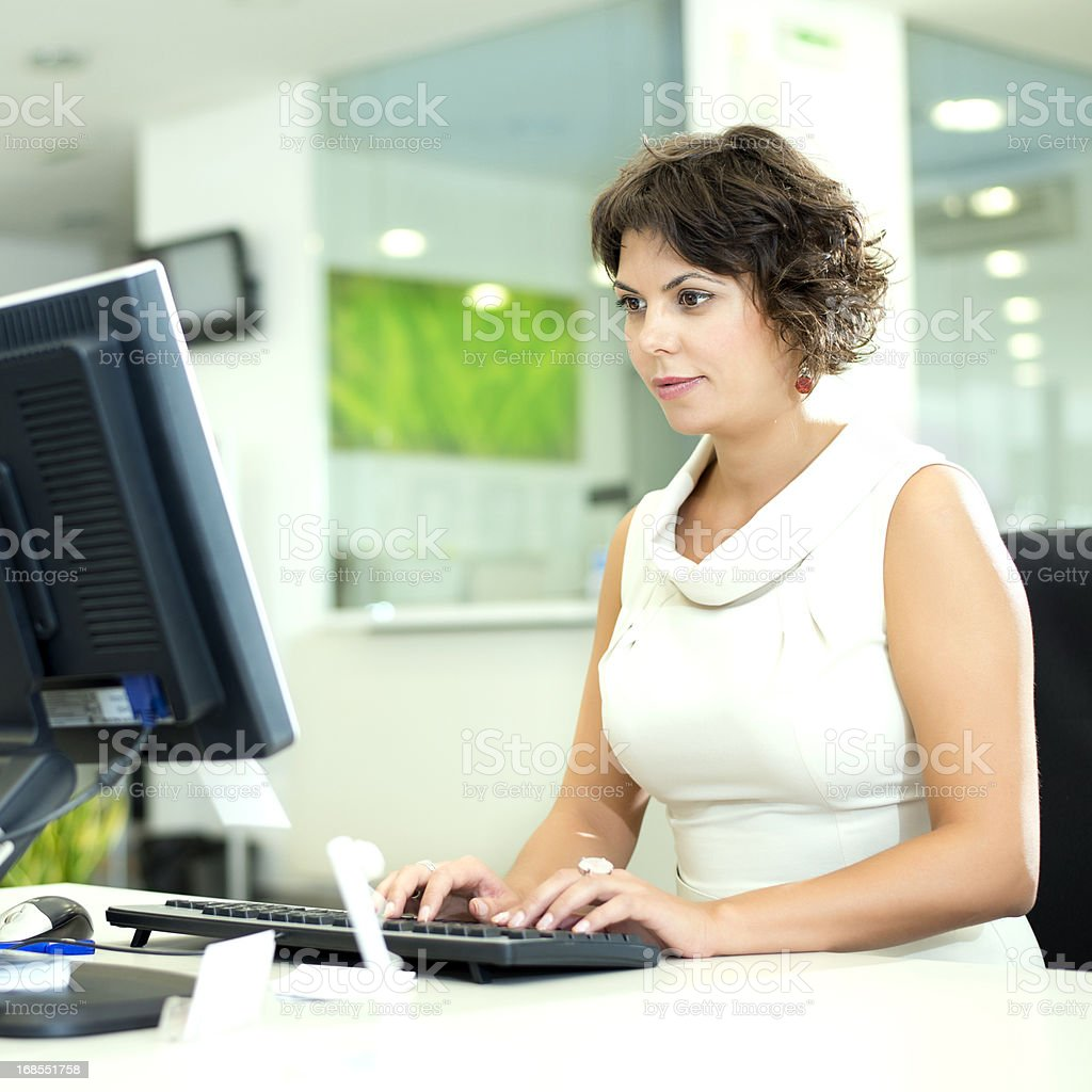 Woman working on a desktop computer royalty-free stock photo