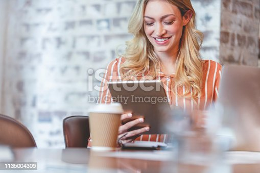 912944158istockphoto Woman working on a digital tablet. 1135004309
