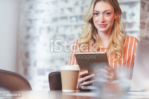 912944158istockphoto Woman working on a digital tablet. 1135004310