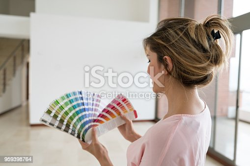 Happy woman working on a housing project and choosing a color to paint the walls