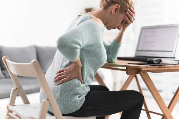 Frau arbeitet auf einem Laptop und hat Kopfschmerzen und Rücken, Hüfte, WirbelsäuleSchmerzen. – Foto
