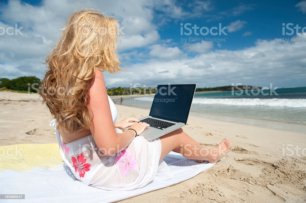 Woman working on a laptop at the beach royalty-free stock photo