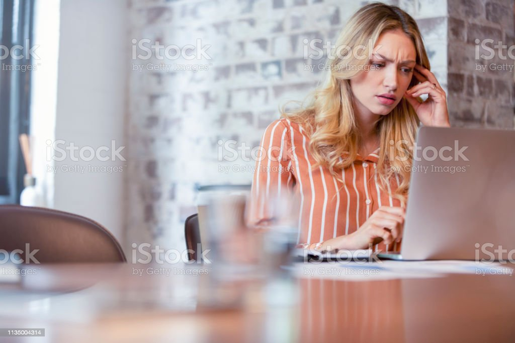 Woman working on a laptop computer. She has blond hair. Woman working on a laptop computer. She has blond hair. She is looking quite serious and worried. There is a brick wall behind her. Copy space Adult Stock Photo