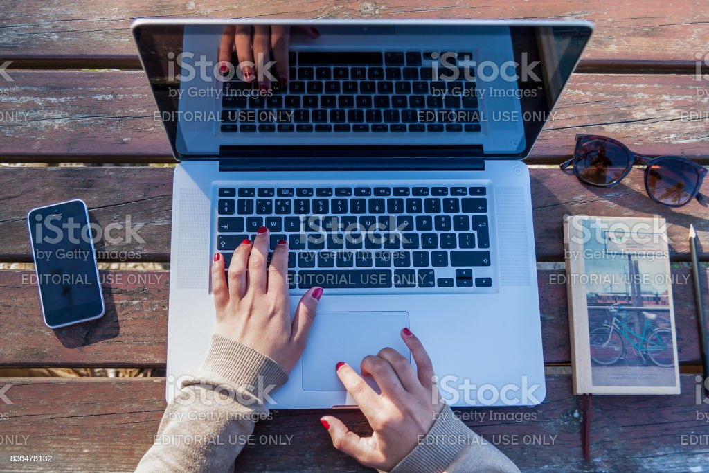 Woman working on a park on her laptop top view on a wood table. stock photo