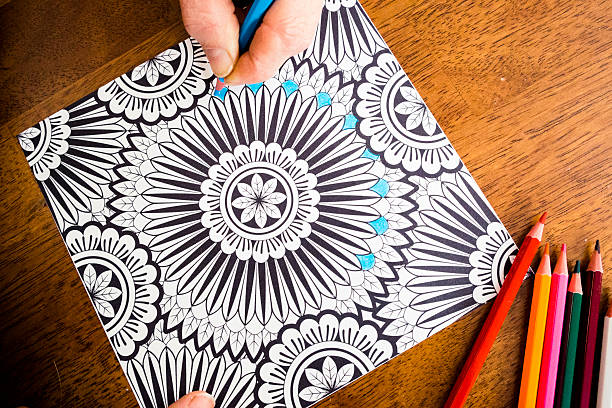 woman working on an adult coloring book design with markers - ausmalbilder für erwachsene stock-fotos und bilder