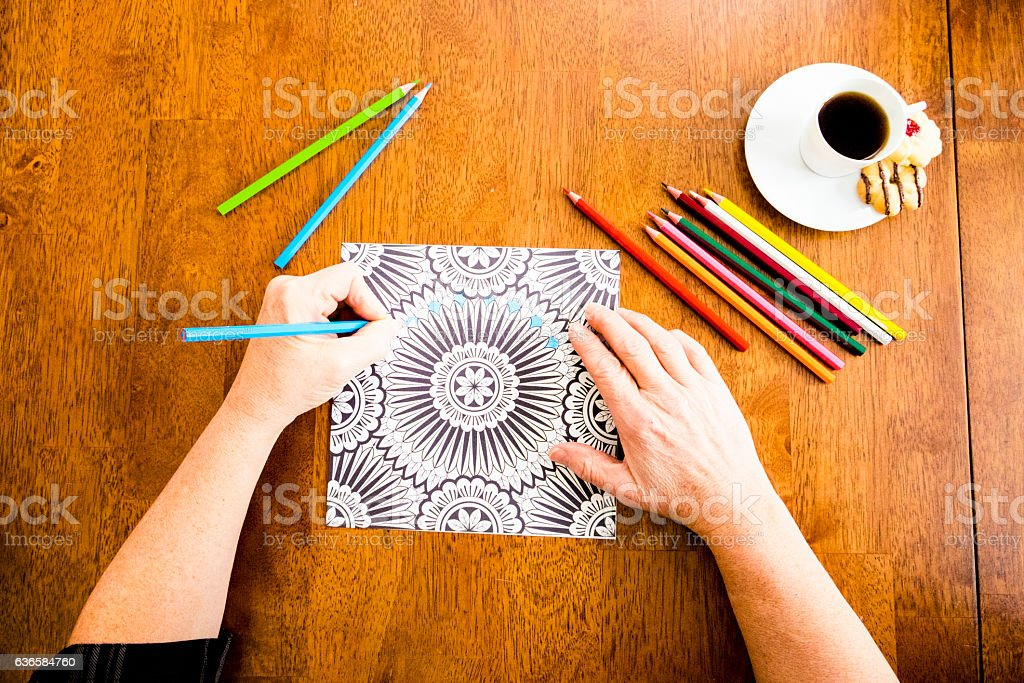 Woman Working On An Adult Coloring Book Design With Markers stock photo